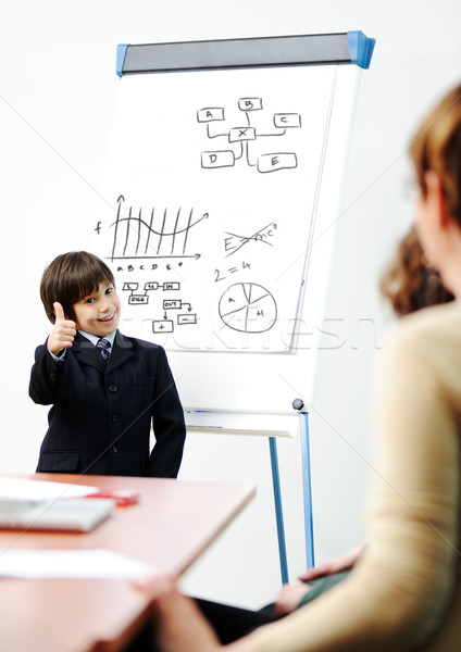 Stock photo: Genius kid on business presentation speaking to adults and giving them a lecture