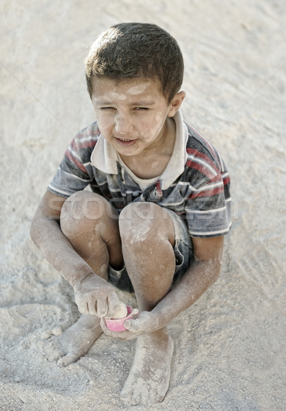 Portrait of poverty, little poor dirty boy playing in sand Stock photo © zurijeta