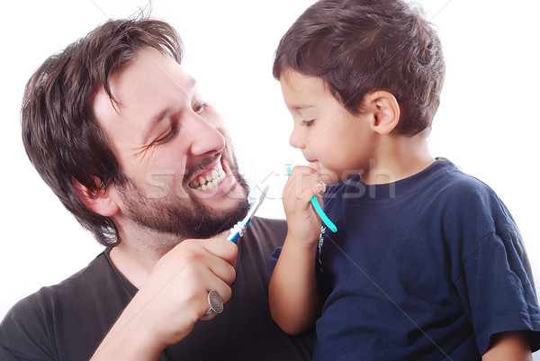 Father teaching his son how to clean the teeth Stock photo © zurijeta