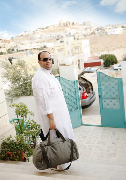 Saudi arabic businessman traveling with his car, holding a bag on stairs Stock photo © zurijeta