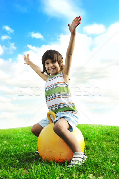 Sporty cute positive kid, playing happily with big ball on green meadow Stock photo © zurijeta