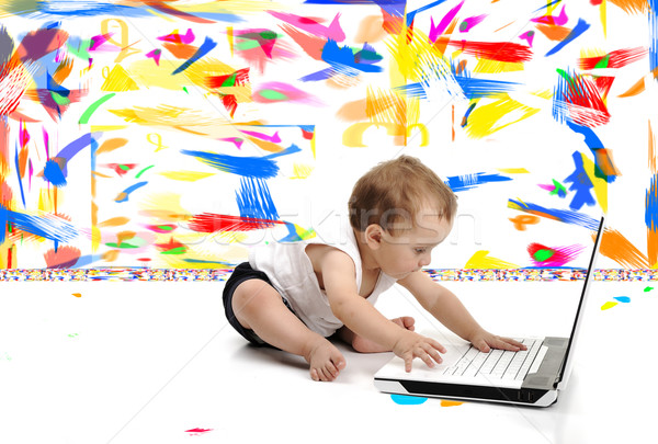 Little baby boy is sitting on floor with his laptop, isolated over white wall, in messy painted room Stock photo © zurijeta