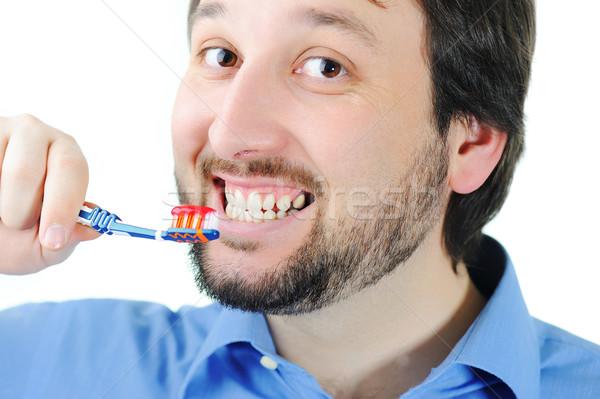 Fiatalember fogmosás közelkép arc férfi száj Stock fotó © zurijeta