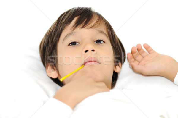 Sick little boy with thermometer, laying on bed Stock photo © zurijeta