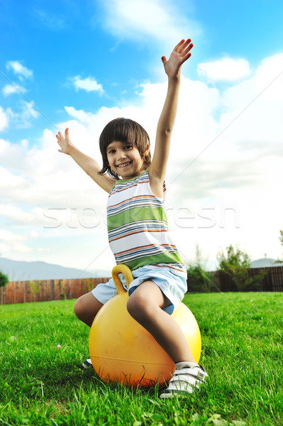 Little happy boy playing with big ball and jumping with wide opened arms in air Stock photo © zurijeta