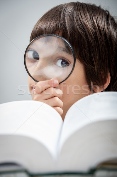 Kid reading and researching the book with magnifier Stock photo © zurijeta