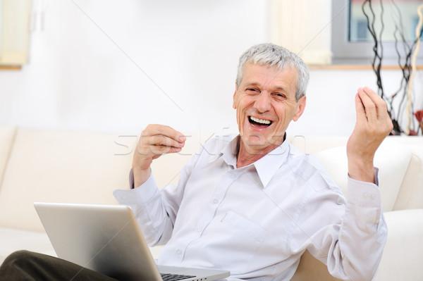 Senior good looking man with laptop at home Stock photo © zurijeta