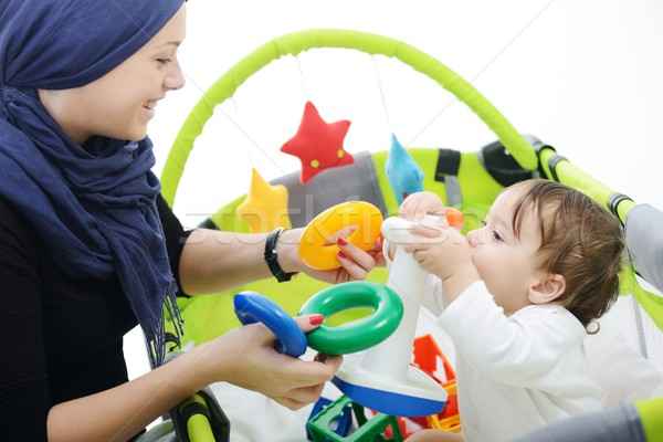 Arabic Muslim mother playing and taking care of her baby Stock photo © zurijeta
