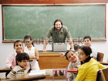 Stock photo: Teacher with children in classroom