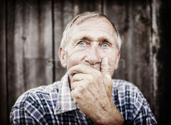 Stock photo: Desperate senior man suffering and covering face with hands in d