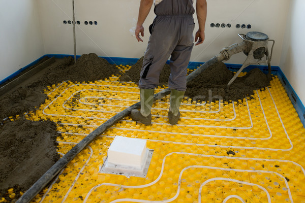 Plasterer at indoor concrete cement floor topping with float Stock photo © zurijeta
