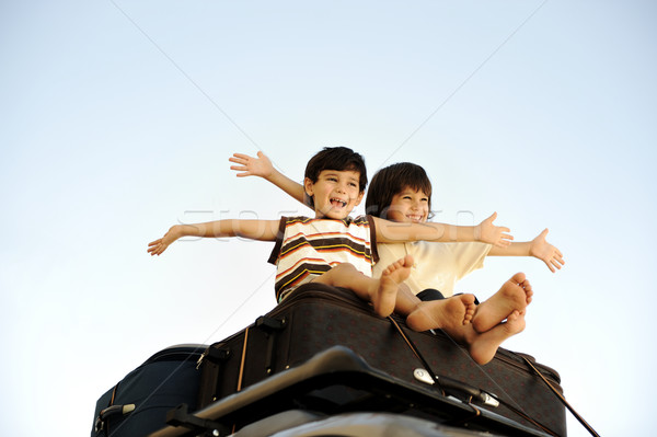 Two little boys traveling on bags, the top of the car Stock photo © zurijeta
