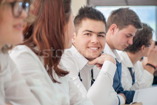 Uśmiechnięty nastolatek posiedzenia klasie inny nastolatków Zdjęcia stock © zurijeta