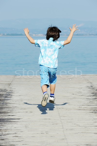 Kid работает прыжки морем док пляж Сток-фото © zurijeta