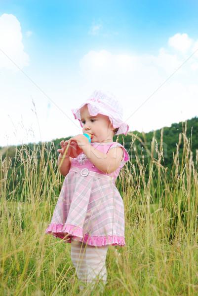 Baby girl standing in nature and drinking milk from bottle Stock photo © zurijeta