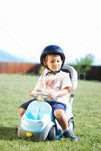 Child on green meadow driving a playing car Stock photo © zurijeta