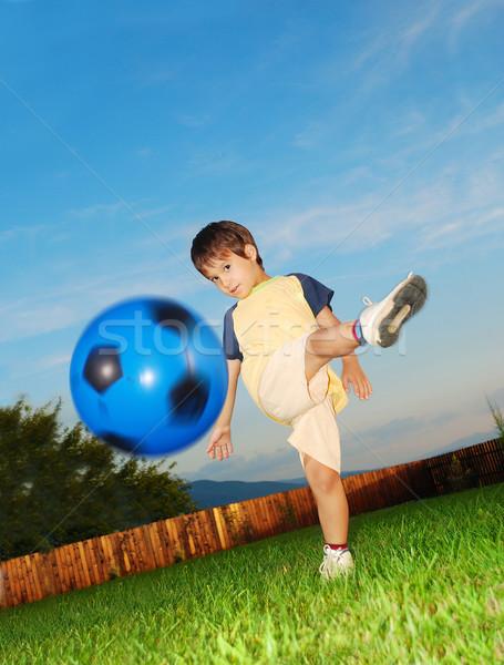 Little cute kid is hitting ball by his foot Stock photo © zurijeta