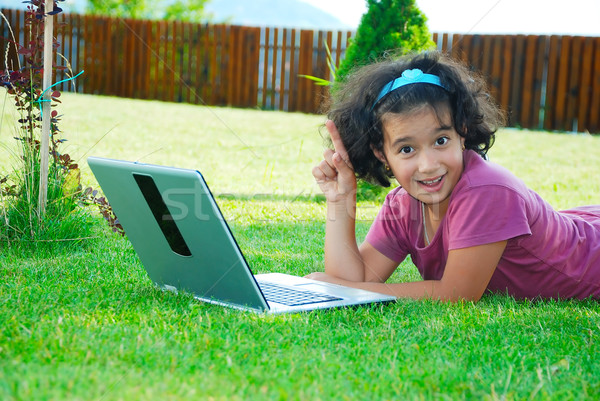 A little cute girl laying down in grass with laptop Stock photo © zurijeta