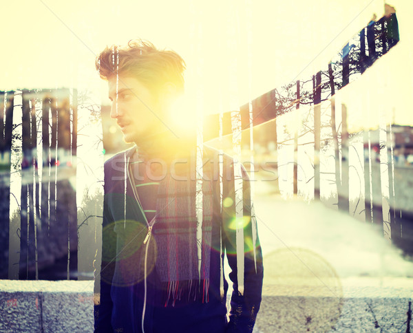 Young man standing on wind in the city at sunset Stock photo © zurijeta