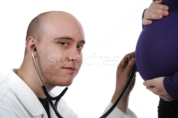 Stock photo: Doctor concentrating on pregnancy examination with stethoscope