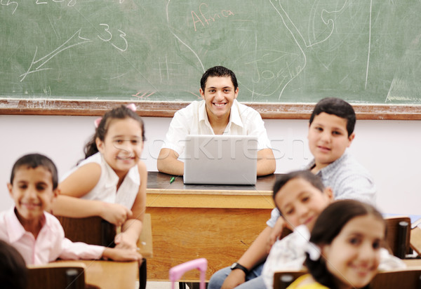 Happy young teacher and children in classroom together Stock photo © zurijeta