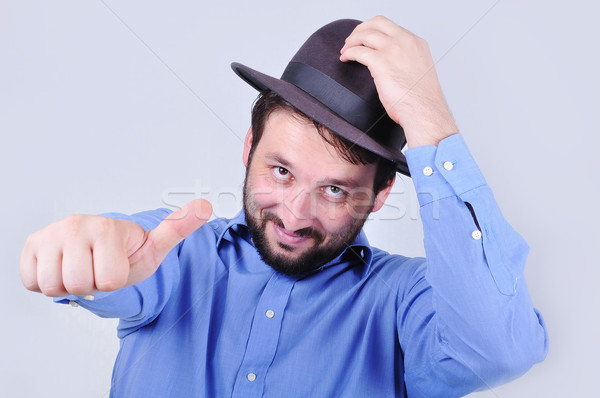 Young man with hat and pointing with his thumb up Stock photo © zurijeta