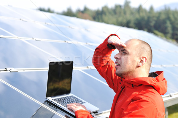 Male engineer at work place, solar panels in background Stock photo © zurijeta
