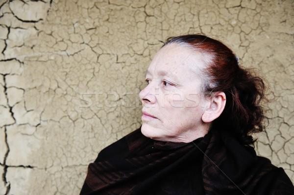 Elderly woman on cracked wall standing and thinking Stock photo © zurijeta