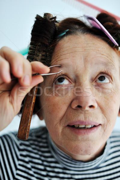 Senior female tweezing eyebrow Stock photo © zurijeta