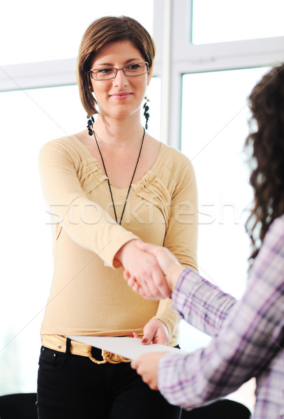 Closing a deal with a female handshake. Signed contract in the hand between women. Stock photo © zurijeta