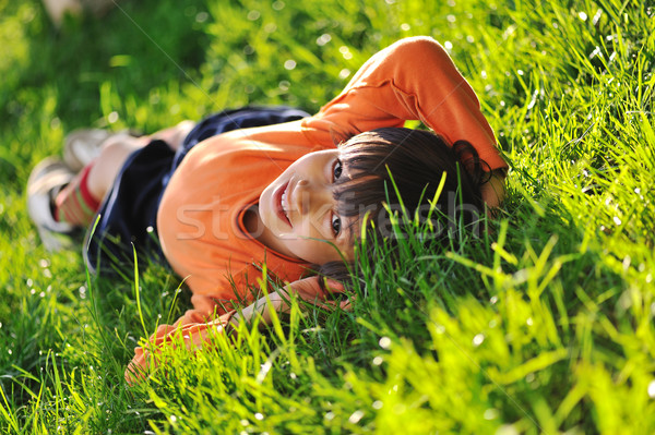 Happy boy laying on beautiful morning green grass Stock photo © zurijeta