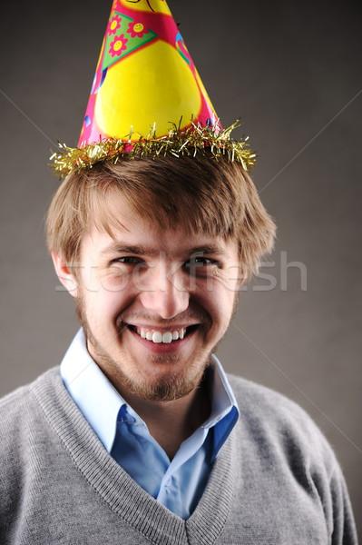 Cheerful young man with birthday celebrating hat smiling Stock photo © zurijeta