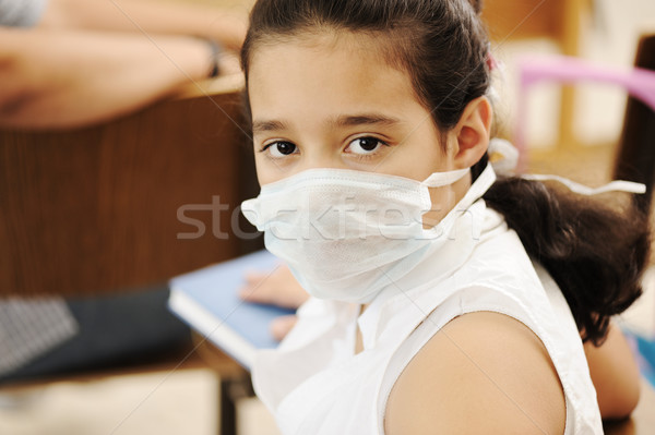 Schoolgirl with medicine mask on face, in classroom, against: virus, ill, epidemic, plague, flu Stock photo © zurijeta