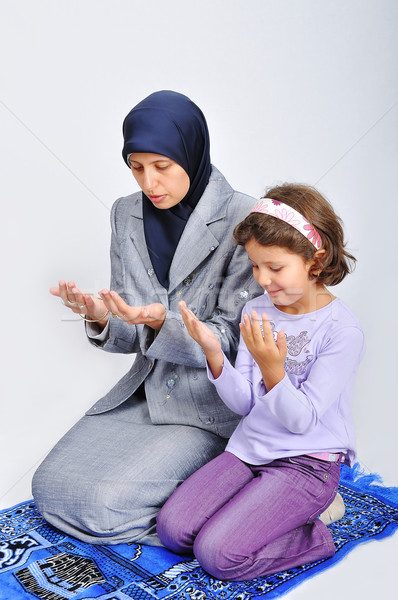 Young muslim woman praying on traditional way with her daughter Stock photo © zurijeta
