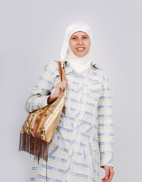 A young muslim woman in traditional clothes caring a bag Stock photo © zurijeta