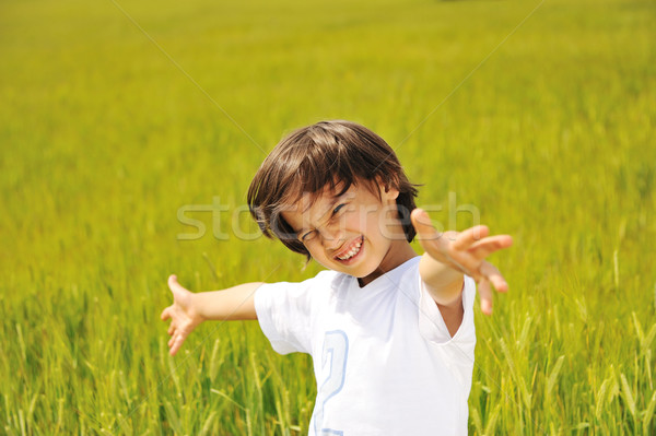 Happy kid on green field with widely opened arms Stock photo © zurijeta