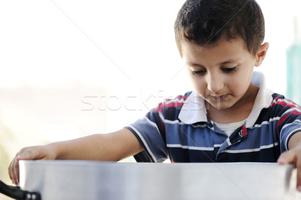 Portrait of poverty, little poor boy on food pot Stock photo © zurijeta