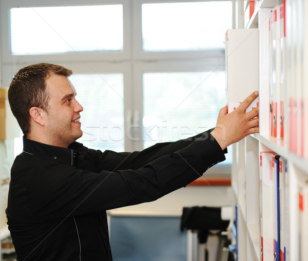 Man folding folders on shelves at office Stock photo © zurijeta