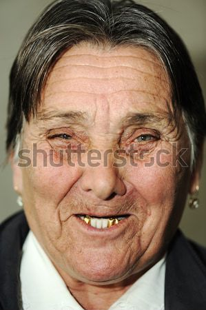 Portrait of laughing funny elderly woman with golden teeth making a grimace Stock photo © zurijeta