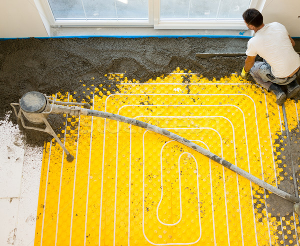Manual worker installing underfloor heating and colling pipes Stock photo © zurijeta