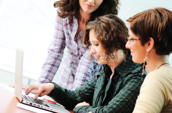 Stock photo: Group of young happy people looking into laptop working on it