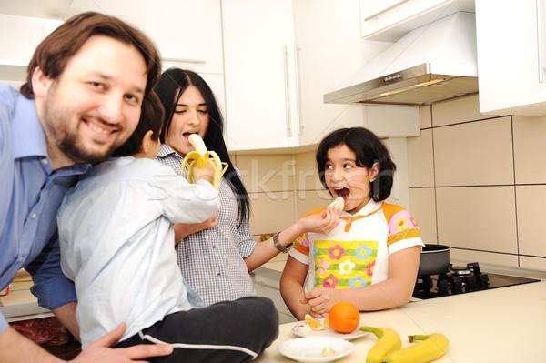 Happy family of four members in kitchen Stock photo © zurijeta