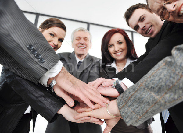 Group of happy smiling executives placing their hands together Stock photo © zurijeta