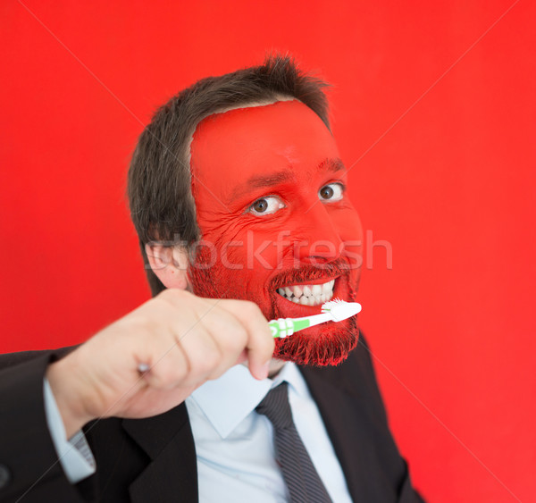 Young man portait with red painted face brushing teeth Stock photo © zurijeta