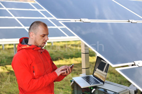 Engineer working with laptop by solar panels, talking on cell phone Stock photo © zurijeta